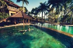 Natação da menina na associação da infinidade no recurso luxuoso, hotel Retrato da mulher que vai para uma nadada na ilha exótica Imagem de Stock