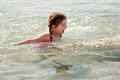 Natação da menina no mar. Imagem de Stock