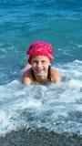 Natação da menina no mar e jogo na tira litoral Fotos de Stock