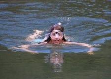 Natação da rapariga com óculos de proteção e snorkel Imagens de Stock
