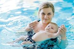 Natação de meia idade feliz da mãe com o bebê adorável bonito na piscina fotos de stock