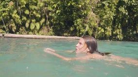 Natação de sorriso da mulher no lago da cachoeira na mulher alegre da floresta úmida tropical que aprecia a nadada na água clara  video estoque