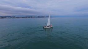 Natação do barco sob velas através do mar contra Batumi, par que está na curva video estoque