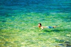 Natação do homem em Crystal Clear Sea Imagem de Stock