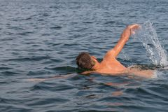 Natação do homem novo no lago imagem de stock
