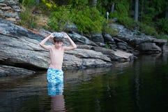 Natação do menino em um fim da tarde do lago Imagens de Stock