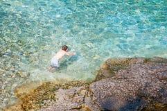 Natação do menino na água claro de turquesa foto de stock
