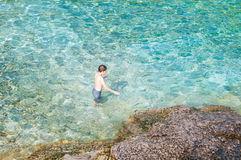 Natação do menino na água claro de turquesa fotografia de stock royalty free