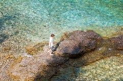 Natação do menino na água claro de turquesa fotografia de stock