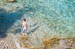 Natação do menino na água claro de turquesa imagens de stock