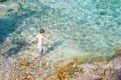 Natação do menino na água claro de turquesa imagem de stock