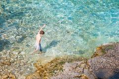 Natação do menino na água claro de turquesa imagem de stock royalty free