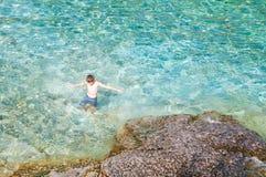 Natação do menino na água claro de turquesa imagens de stock royalty free
