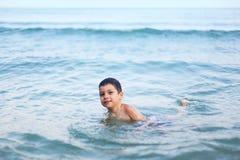 Natação do menino no mar imagens de stock royalty free