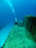 Natação do mergulhador ao longo do lado um Shipwreck Sunken Fotos de Stock Royalty Free
