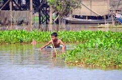 Natação do rapaz pequeno na bacia de alumínio na água enlameada da seiva de Tonle do rio Foto de Stock