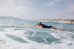 Natação do surfista da mulher no mar Imagem de Stock Royalty Free