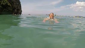 Natação feliz do homem na câmera pov da ação da água do mar do indivíduo novo na praia bonita video estoque