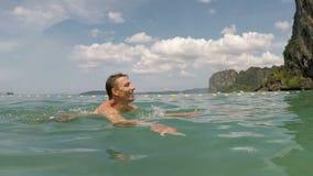 Natação feliz do homem na câmera pov da ação da água do mar do indivíduo novo na praia bonita filme