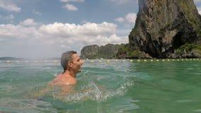 Natação feliz do homem na câmera pov da ação da água do mar do indivíduo novo na praia bonita vídeos de arquivo