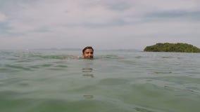 Natação latino-americano do homem na câmera pov da ação da água do mar do indivíduo novo na praia bonita video estoque