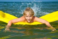 Natação nova do menino no colchão no mar foto de stock