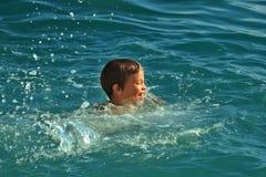 Natación adolescente del muchacho en el día soleado caliente del mar o del océano en agua pura con las ondas Fotografía de archivo