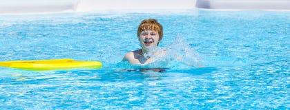 Natación adolescente del muchacho en una piscina Imágenes de archivo libres de regalías