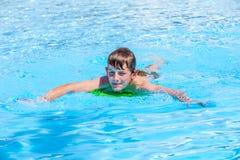 Natación adolescente del muchacho en una piscina Foto de archivo