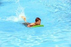 Natación adolescente del muchacho en una piscina con un tablero de la boogie Fotografía de archivo