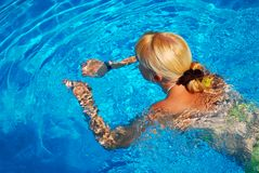 Natación adulta joven de la muchacha en la piscina Fotografía de archivo libre de regalías