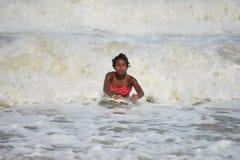 Natación afroamericana de la muchacha en olas oceánicas Fotos de archivo