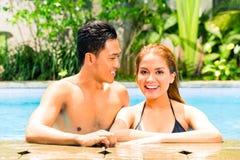 Natación asiática de los pares en piscina del centro turístico fotos de archivo libres de regalías