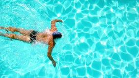 Natación atlética del nadador a través de la piscina de arriba almacen de metraje de vídeo