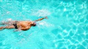 Natación atlética del nadador a través de la piscina de arriba metrajes