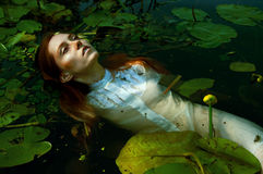 Natación blanda de la mujer joven en la charca entre lirios de agua Fotografía de archivo