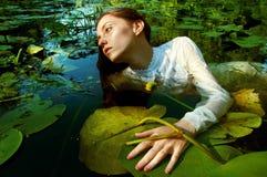 Natación blanda de la mujer joven en la charca entre lirios de agua Foto de archivo libre de regalías