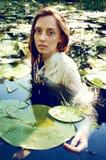 Natación blanda de la mujer joven en la charca entre lirios de agua Fotos de archivo libres de regalías