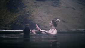 Natación cariñosa joven de los pares en aguas termales junto Hombre y mujer que se relajan en el agua en valle de la montaña en I almacen de metraje de vídeo