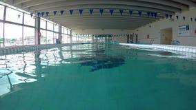 Natación caucásica de mediana edad del hombre en el agua, en la piscina en Palamos en España almacen de video