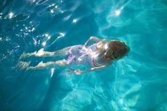 Natación de la chica joven en la piscina Foto de archivo libre de regalías