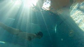 Natación de la muchacha debajo del agua contra la luz en la piscina almacen de metraje de vídeo