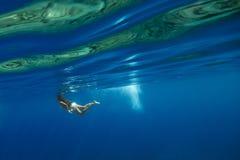 Natación de la muchacha en agua azul Foto de archivo