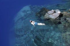 Natación de la muchacha en el lago crater Imágenes de archivo libres de regalías
