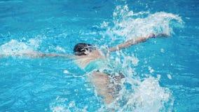 Natación de la muchacha en la piscina azul almacen de video