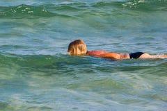 Natación de la muchacha en las ondas del mar en los rayos del verano imagenes de archivo