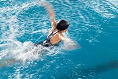 Natación de la muchacha en la piscina imagenes de archivo