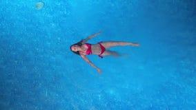 Natación de la muchacha en la piscina metrajes