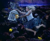 Natación de la muchacha en un fishtank Imagen de archivo