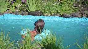 Natación de la muchacha en una pequeña charca El niño goza del agua fresca en un día de verano caliente Niñez feliz Las flores y  almacen de metraje de vídeo